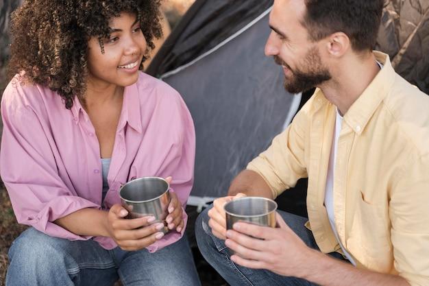 Couple de smiley à l'extérieur, prendre un verre