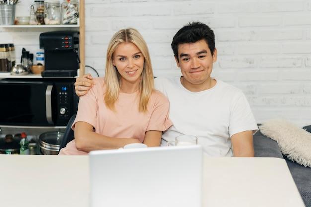 Couple de smiley à la maison pendant la pandémie à la recherche d'un ordinateur portable