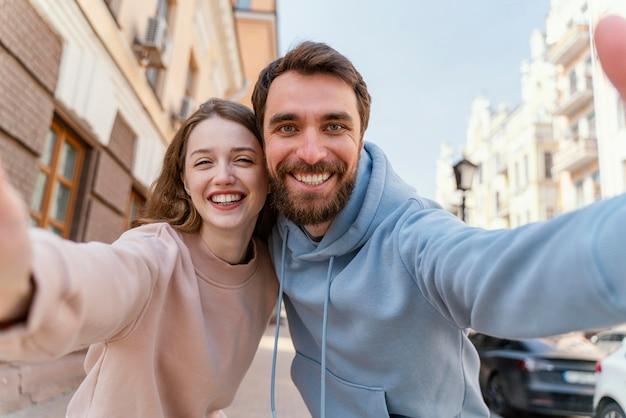 Couple de smiley prenant un selfie ensemble à l'extérieur dans la ville