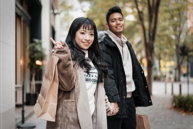 Couple de smiley avec sac à provisions dans la rue
