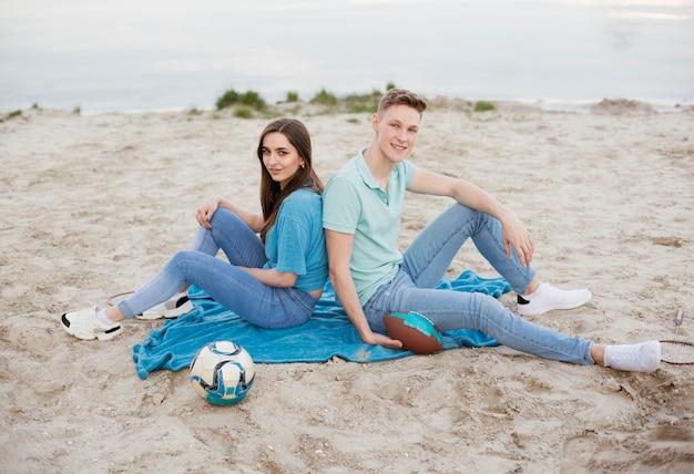 Couple de smiley de tir complet assis sur une couverture