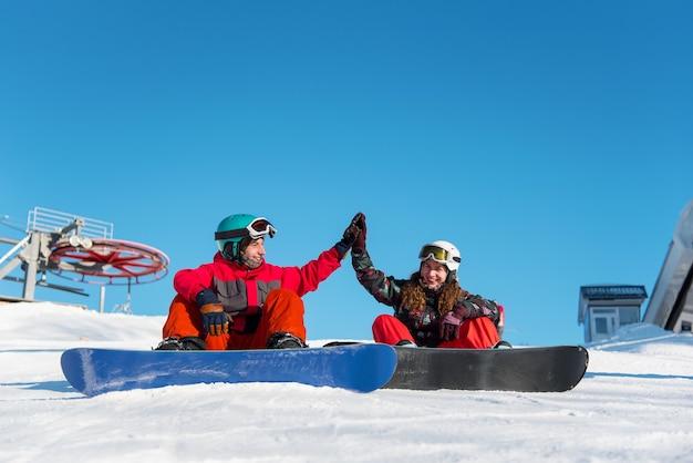 Couple de snowboardeurs dans la montagne