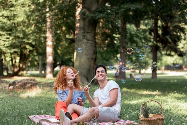 Couple soufflant des bulles dans le parc