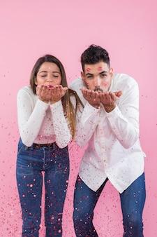 Couple soufflant des confettis des mains