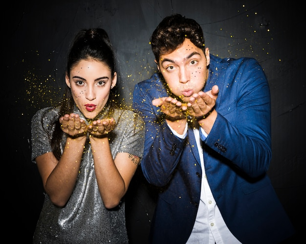 Couple soufflant des paillettes d'or