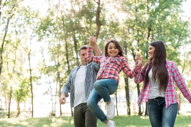 Couple soulevant leur fille en se promenant dans le parc