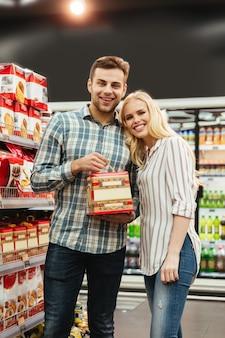 Couple souriant, acheter de la nourriture pour noël