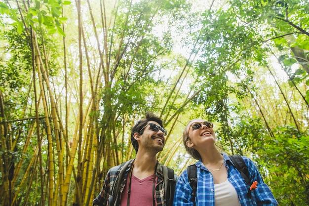 Couple souriant admirait la forêt