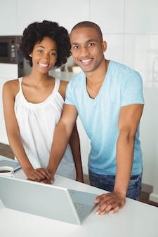 Couple souriant à l'aide d'un ordinateur portable dans la cuisine sur le comptoir