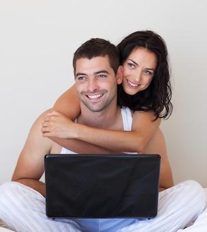 Couple souriant à l'aide d'un ordinateur portable sur un lit