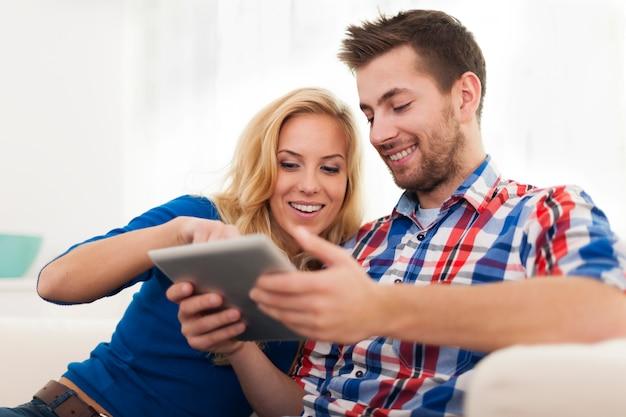 Couple souriant à l'aide de tablette numérique à la maison