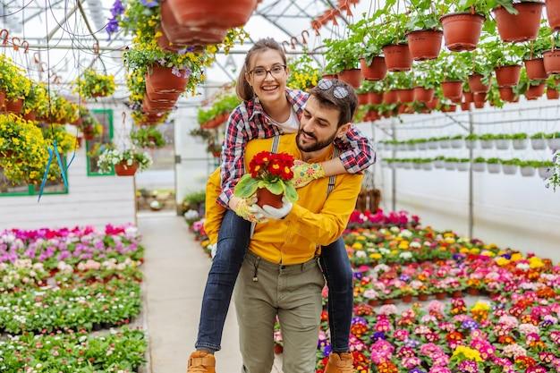 Couple souriant amoureux ayant ferroutage en serre. tout autour d'eux sont des fleurs colorées. propriétaires de petites entreprises.