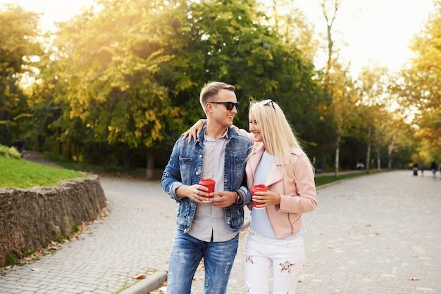 Couple souriant amoureux marchant dans le parc automne, main dans la main. écoutez de la musique avec des écouteurs et buvez du café.
