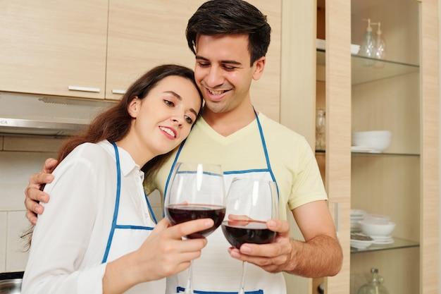 Couple souriant, appréciant le vin rouge