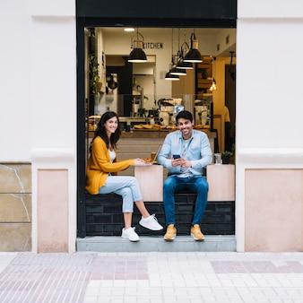 Couple souriant, assis dans la zone de la cafétéria ouverte