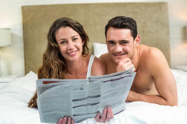 Couple souriant au lit avec un journal