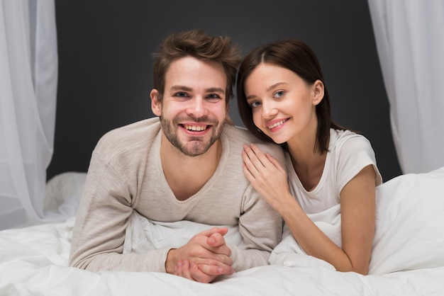 Couple souriant au lit