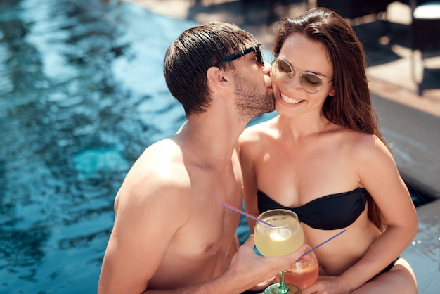 Couple souriant, buvant des cocktails au bord de la piscine