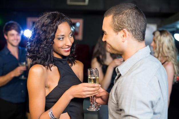 Couple souriant, buvant du champagne