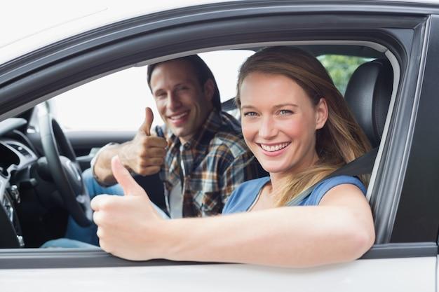 Couple souriant à la caméra avec le pouce levé
