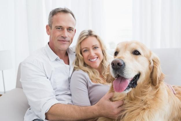 Couple souriant caresser leur golden retriever sur le canapé