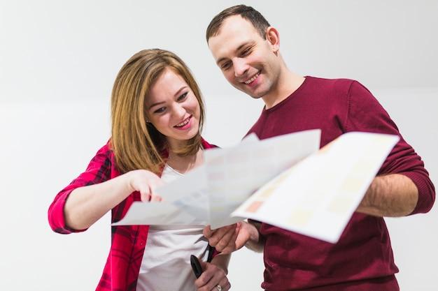 Couple souriant, choisissant la couleur pour la peinture murale