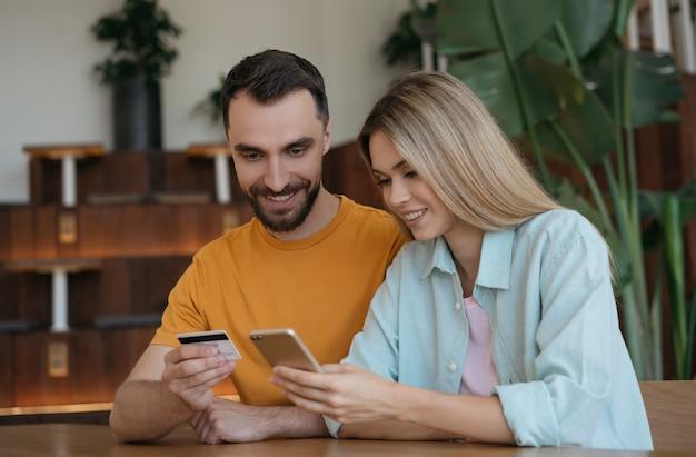 Couple souriant, commande de nourriture assis à la maison, concept de livraison. amis détenant des achats en ligne par carte de crédit