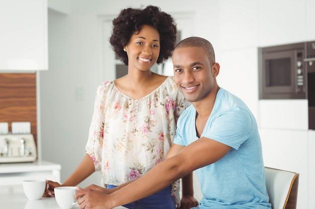 Couple souriant dans la cuisine en regardant la caméra