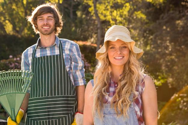 Couple souriant dans le jardin tenant un râteau