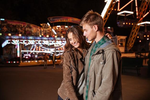 Couple souriant dans un parc d'attractions.