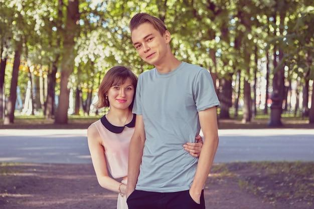 Un couple souriant a une date au parc public.