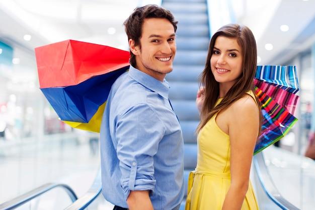 Couple souriant sur l'escalator dans le centre commercial