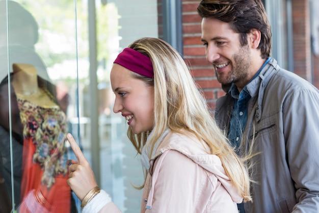 Couple Souriant, Faire Du Lèche-vitrine Et Pointant Sur Les Vêtements Photo Premium