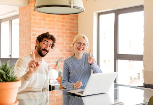Couple souriant fièrement et avec confiance en faisant le numéro un pose triomphalement, se sentant comme un chef de file