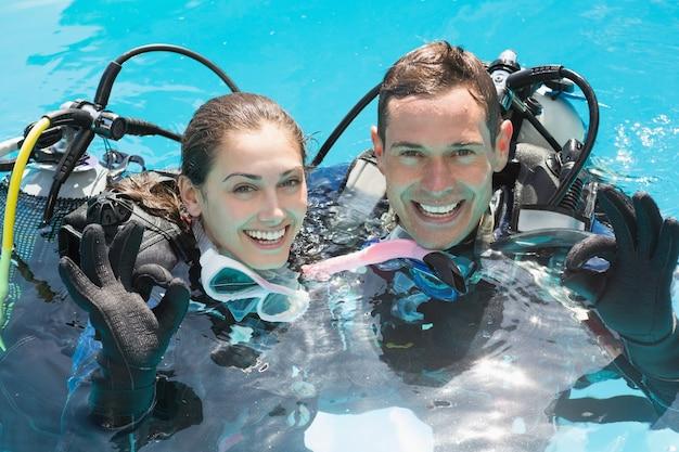 Couple souriant sur la formation de plongée dans la piscine montrant le geste ok