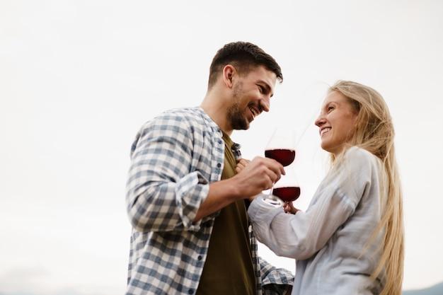 Couple souriant grillant des verres à vin à l'extérieur dans les montagnes