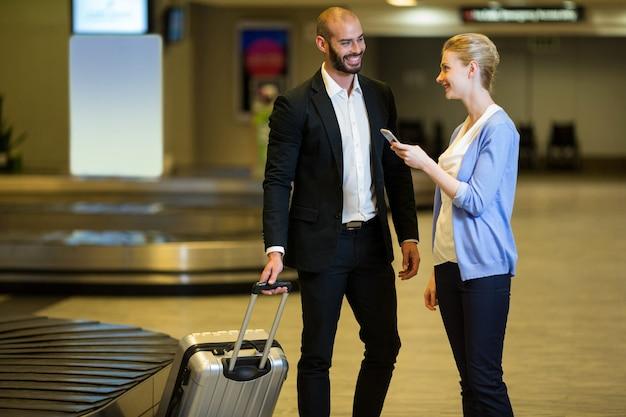 Couple souriant interagissant les uns avec les autres dans la zone d'attente