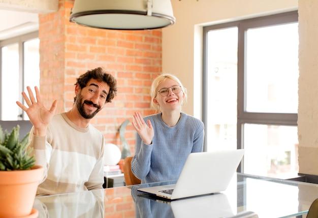 Couple souriant joyeusement et gaiement, en agitant la main et en vous saluant, ou en disant au revoir