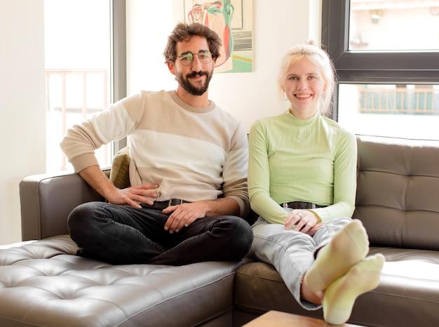 Couple souriant joyeusement avec une main sur la hanche et une attitude confiante, positive, fière et amicale