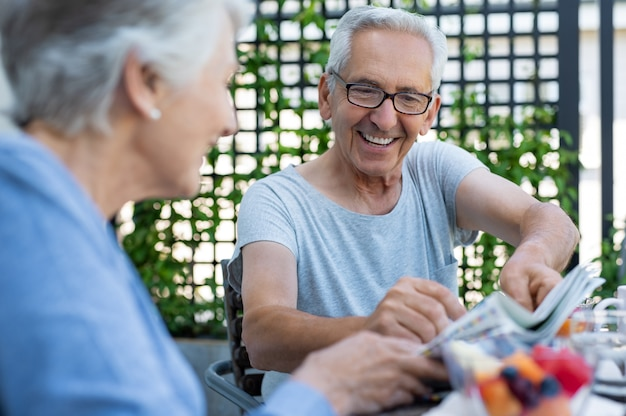 Couple souriant, lisant le journal