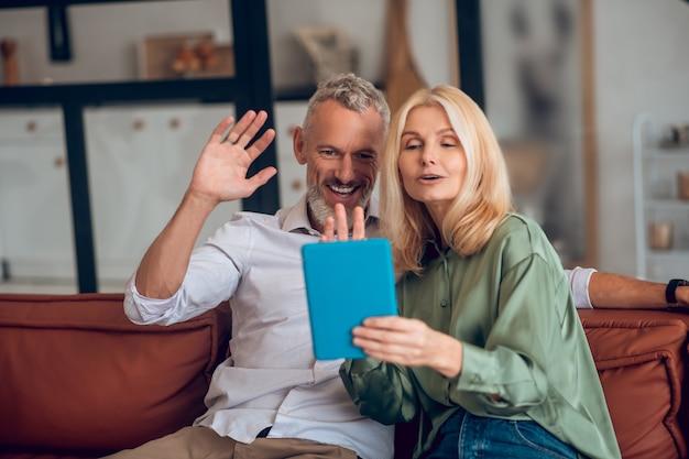 Couple souriant à lunettes de soleil assis sur le canapé et ayant un chat vidéo