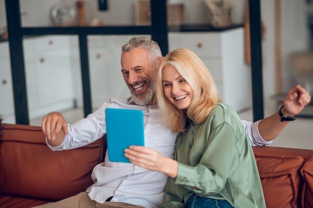 Couple souriant à lunettes de soleil assis sur le canapé et parler en ligne