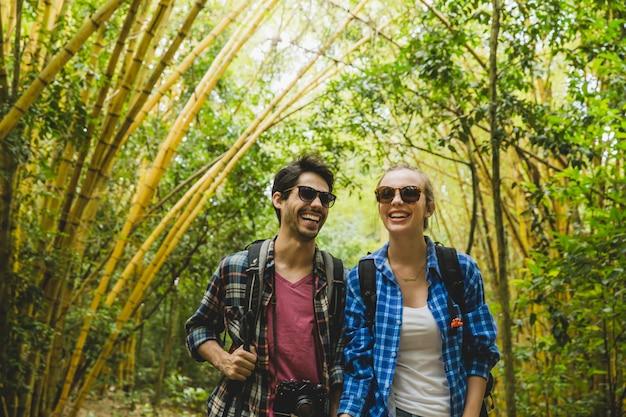 Couple souriant marchant dans la forêt de bambous