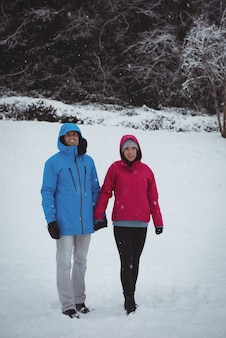 Couple souriant marchant dans la forêt enneigée