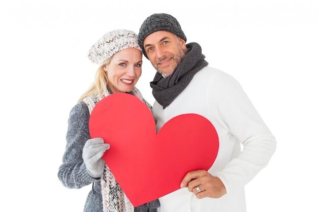 Couple souriant en mode hiver posant avec forme de coeur