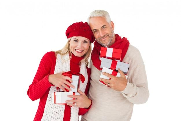 Couple souriant en mode hiver tenant des cadeaux