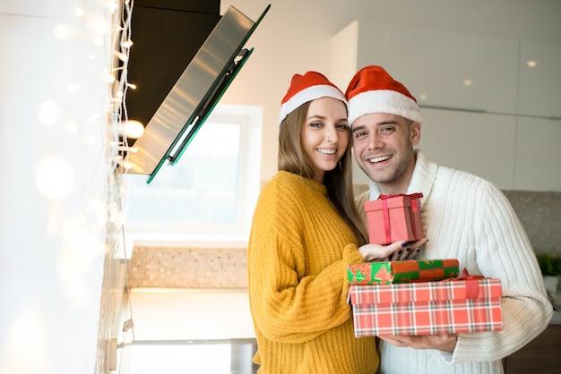 Couple souriant avec le nouvel an présente dans la cuisine