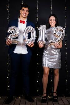 Couple souriant avec numéros de ballons