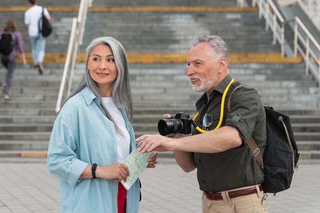 Couple souriant à plan moyen avec appareil photo