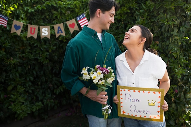 Couple souriant de plan moyen avec bouquet